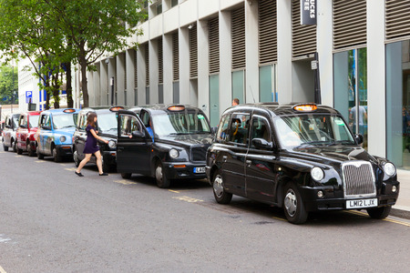 taxicab: LONDON - JUL 2, 2015: Row of London Taxis lined up along the sidewalk. The Londons iconic black cabs are a symbol of the city and a major attraction in themselves.
