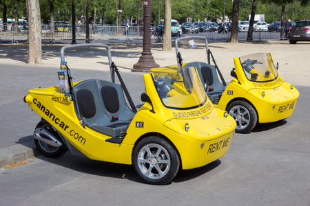 twoseater: PARIS - JUN 19, 2015: Small two-seater convertible cars with an audio-guided system for rent to tourists in Paris. These vehicles from Canaricar drive at max 50 kmh.