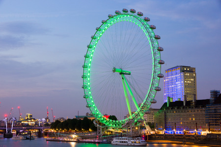 LONDON - JUL 1, 2015: Evening view on the illuminated London Eye. The ferris wheel is a famous tourist attraction and with a height of 135 metres 443 ft the biggest in Europe.