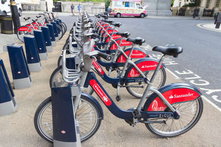 santander: LONDON - APR 6, 2015: Row of rental bikes from Santander Cycles. Santander Cycles is Londons self-service, bike-sharing scheme for short journeys. Editorial
