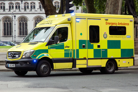 LONDON - JUL 1, 2015: Emergency Ambulance speeds along a street in London in response to an emergency call.