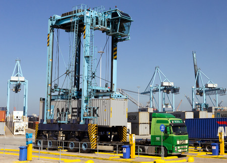 straddle: ROTTERDAM, NETHERLANDS - SEP 7, 2012: A Straddle carrier adding a container on the trailer of a waiting truck.