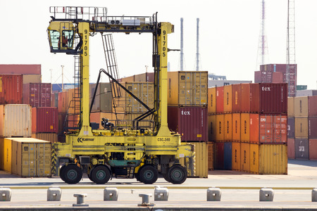 dockside: ANTWERP, BELGIUM - JUL 9, 2013: Straddle carrier moving shipping containers in the Port of Antwerp. Editorial
