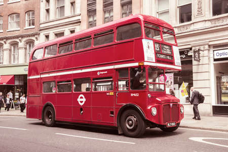 english famous: LONDON - JUL 02, 2015: Vintage red double-decker bus in a street of London, UK.