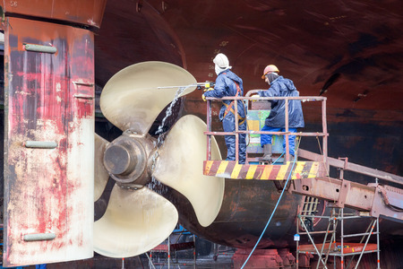 docks: ROTTERDAM, NETHERLANDS - SEP 5, 2015: Workers removing algue in ship repair dry dock.