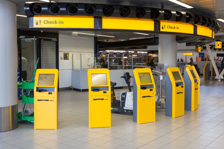 airport check in counter: AMSTERDAM, NETHERLANDS - JUL 31, 2014: Self check-in machines at Schiphol airport.