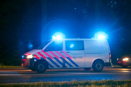 blue lights: VARSSEVELD, NETHERLANDS - OCT 29, 2015: A Dutch police car with emergency lights holding traffic during a car accident.