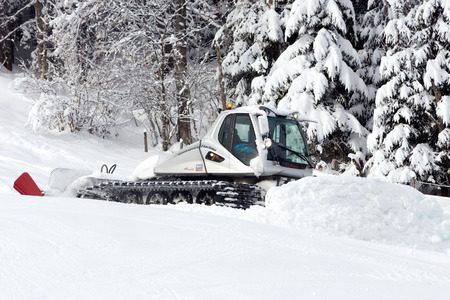 piste: FLACHAU, AUSTRIA - JAN 7: Snow groomer on the ski piste in the ski resort town of Flachau, Austria on Jan 7, 2012. These pistes are part of the Ski Armad network, the largest of Europe.