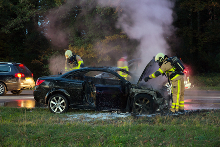 Firefighters near a  burned out car wreck