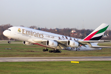 air plane: DUSSELDORF, GERMANY: DEC 17, 2015: Emirates Airbus A380 take off from Dusseldorf airport. Soccer players of Real Madrid are painted on the airplane to show the partnership between Emirates and Real Madrid. Editorial