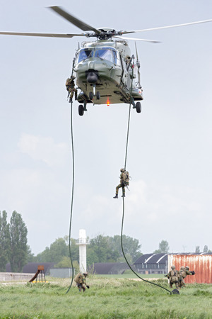 heli: BEAUVECHAIN, BELGIUM - MAY 20, 2015: The new Belgian army NH90 helicopter dropping soldiers at Beauvechain airbase. The first helicopters entered service in 2013
