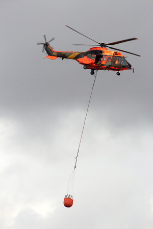 TORREJON, SPAIN - OCT 11, 2014: Spanish Air Force Eurocopter Cougar helicopter with a water bucket for firefighting Editorial
