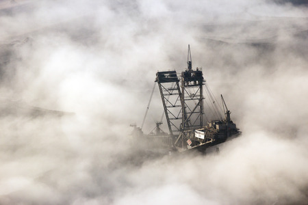 open pit: HAMBACH, GERMANY - DEC 14, 2015: Bucket-wheel excavator number 289 from RWERheinbraun standing idle in the morning mist in the open pit mine Tagebau Hambach.