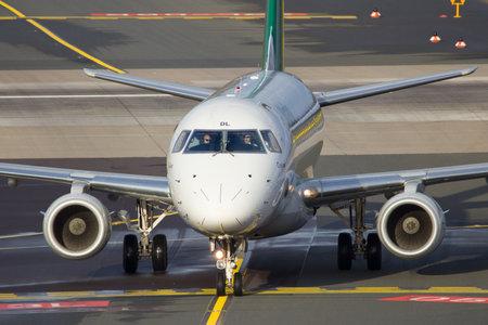 ei: DUSSELDORF, GERMANY - DEC 21, 2015: Alitalia Cityliner Embraer ERJ-175STD taxiing after landing at Dusseldorf Airport