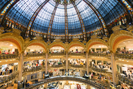french fancy: PARIS, FRANCE - JUNE 18, 2015: Interior of the Galeries Lafayette in Paris. The architect Georges Chedanne designed the store where a Art Nouveau glass and steel dome was finished in 1912