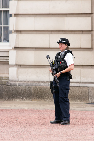 buckingham: LONDON - JUL 1, 2015: Armed police woman in front of Buckingham Palace. Editorial