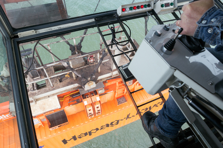 heavy equipment operator: ROTTERDAM - SEP 9, 2015: Gantry crane operator moving a sea container in the Port of Rotterdam.