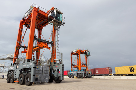 straddle: ROTTERDAM - SEP 6, 2015: Straddle carrier moving a container in a container terminal in the Port of Rotterdam