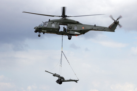 heli: BEAUVECHAIN, BELGIUM - MAY 20, 2015: Belgian army NH90 helicopter transporting an artillery piece