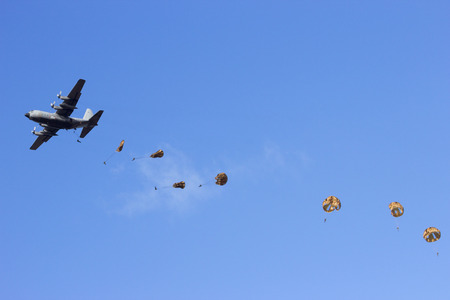 military invasion: Military plane dropping paratroopers Stock Photo