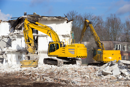 machinery machine: Demolition cranes dismantling a building
