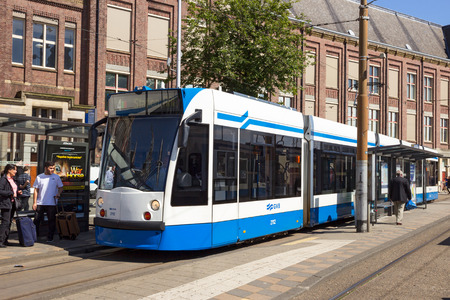 holland: AMSTERDAM - AUG 27, 2014: Public transport company GVB tram in front of Amsterdam Central Station. The citys Tram network is the largest tram network in the Netherlands