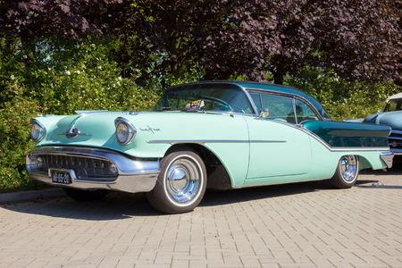 coupe: DEN BOSCH, THE NETHERLANDS - MAY 10, 2016: Parked 1957 Oldsmobile Starfire 98 Holiday Coupe