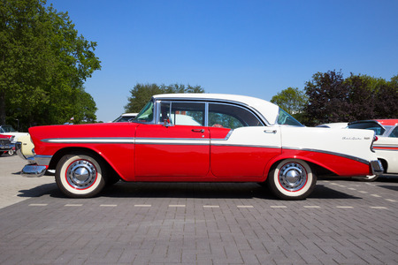 DEN BOSCH, THE NETHERLANDS - MAY 10, 2016: Side view of a parked red and white 1956 Chevrolet Belair 4-door hardtop