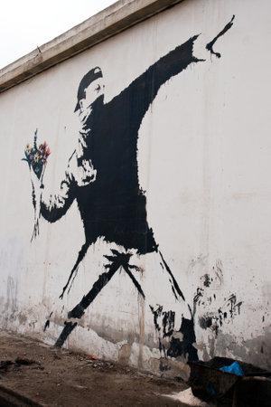 palestinian: BETHLEHEM, PALESTINIAN TERRITORIES - JANUARY 25: Banksy grafitti on a wall in the occupied territories. Bethlehem, January 25, 2010.