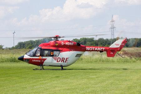 heli: AHLEN, GERMANY - JUN 5, 2016: DRF Luftrettung (German Air Rescue) BK-117 helicopter landing at Ahlen-Nord heliport
