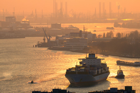 meuse: ROTTERDAM, NETHERLANDS - MAR 16, 2016: Maersk container ship on the Meuse river in the Port of Rotterdam during sunset
