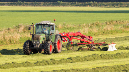 mowing grass: ACHTERHOEK, NETHERLANDS - AUG 16, 2016: Fendt tractor mowing grass farmland