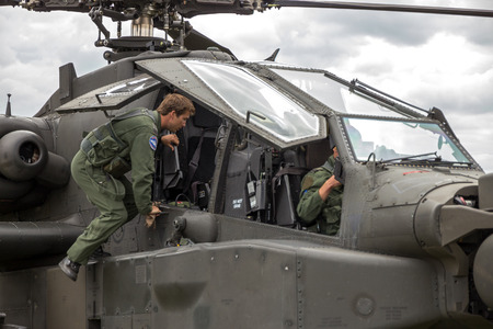apache: GILZE-RIJEN, NETHERLANDS - JUN 20, 2014: Pilot getting into an AH-64 Apache attack helicopter. Editorial