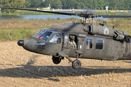 blackhawk helicopter: GRAVE, NETHERLANDS - SEP 17, 2014: American Army Blackhawk helicopter landing in a field.
