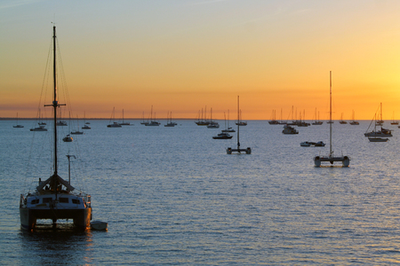 australia: Catamarans in a bay at sunset over sea. Darwin, Australia