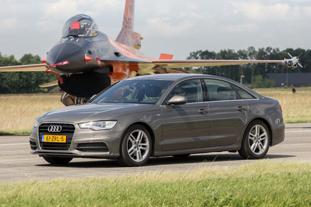 a6: VOLKEL, NETHERLANDS - JUN 15, 2013: Audi A6 Limousine driving in front of a Dutch F-16 fighter jet during the Royal Netherlands Air Force Open Day. Editorial