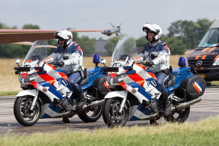 patrolling: VOLKEL, NETHERLANDS - JUN 15, 2013: Dutch military police (Marechaussee) officers patrolling on their bike at the Royal Netherlands Air Force Open Day.