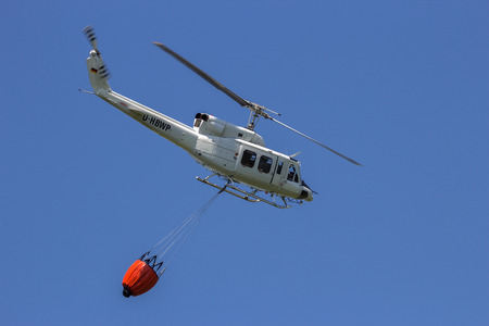 firefighting: AHLEN, GERMANY - JUN 5, 2016: Bell 212 Huey helicopter with a bambi bucket for fire fighting
