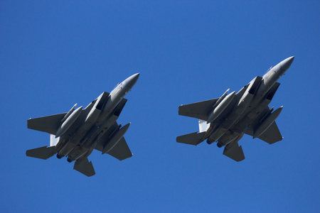 Two fighter jets flying in formation with a blue sky background