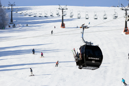 wintersport: FLACHAU, AUSTRIA - DEC 29, 2012: Ski lift cable booth going up the piste in the Austrian Alps. These pistes are part of the Ski Armada network, the largest of Europe.