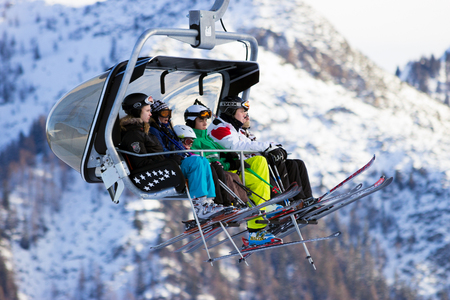 wintersport: FLACHAU, AUSTRIA - DEC 27, 2012: Skiiers on a ski lift to a piste in the Austrial Alps. These pistes are part of the Ski Armada network, the largest of Europe