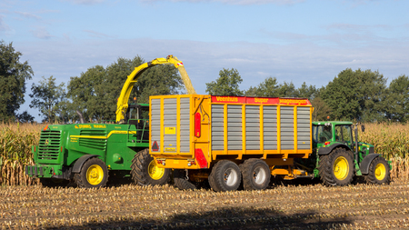 RUURLO, THE NETHERLANDS - SEP 19, 2016: John Deere 6930 tractor and John Deere 7480i Forage Harvester at work.