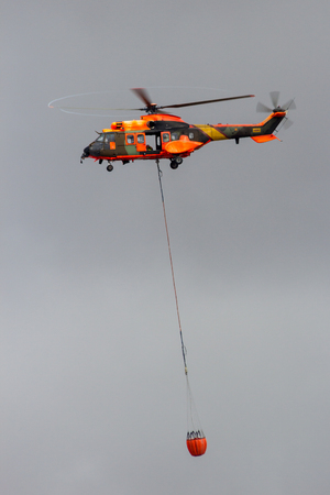 TORREJON, SPAIN - OCT 11, 2014: Spanish Air Force Eurocopter Cougar helicopter with a bambi bucket filled with water, used for aerial firefighting. Editorial