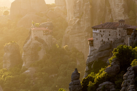 Beautiful scenic sunset view of the Rousanou (St. Barbara) Monastery and St. Nicholas Anapausas Monastery on a monolithic pillar in Meteora, Greece