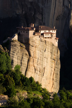 kalampaka: Scenic view of the Orthodox Monastery of Rousanou (St. Barbara) on a monolithic pillar, with a dark shadow background in Meteora, Pindos Mountains, Greece