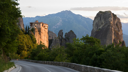 kalabaka: Road and scenic sunset view of the Orthodox Monastery of Rousanou (St. Barbara) on a monolithic pillar in Meteora, Pindos Mountains, Greece