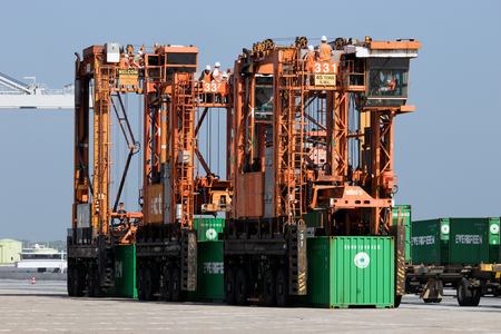 ROTTERDAM - SEP 6, 2015: Straddle carriers moving containers in a shipping terminal in the Port of Rotterdam Editorial