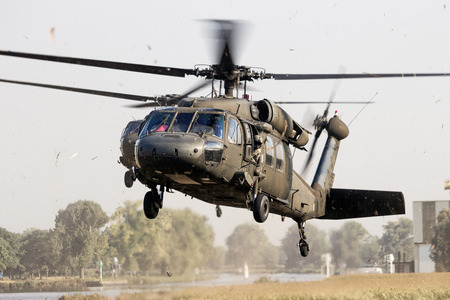 GRAVE, NETHERLANDS - SEP 17, 2014: Two American Army Blackhawk helicopters landing in a field. 新闻类图片