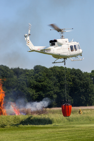 AHLEN, GERMANY - JUN 5, 2016: Bell 212 Huey helicopter during a fire fighting demonstration at Ahlen-Nord heliport