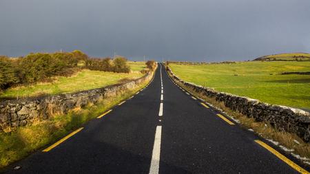 irish countryside: Road through rural Ireland with a gloomy sky.